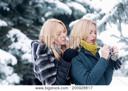 Woman hugging twin sister who warming hands with gloves. Girls with blond hair in forest on winter day. Family care concept. Active lifestyle and vacation. Christmas and new year