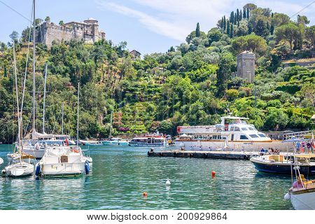PORTOFINO, ITALY - JUNE 26, 2017: Daylight view to beauties of Portofino, Italy. Ships on water with people resting in them.