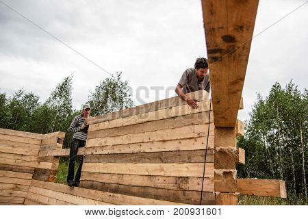 Russia Siberiya - 1.09.2013: Construction worker framing the roof of a country house with help of a crane