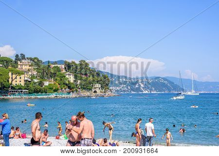 SANTA MARGHERITA LIGURE, ITALY - JUNE 26, 2017: Beautiful sunny day on Santa Margherita Ligure beach in Italy. Tourists and people relaxing and swimming in water