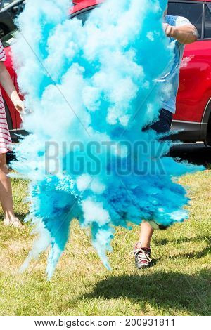 Parents to be kick a soccer ball which explodes with blue powder to reveal that their baby is going to be a boy.