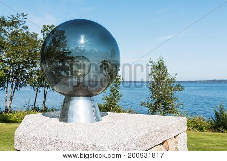 A glass orb with a lightbulb inside and a view of Penobscot Bay with the sun and trees reflecting off of the glass.
