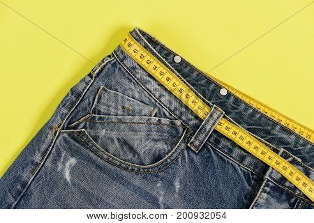 Healthy Lifestyle And Dieting Concept: Denim Trousers With Measure Tape