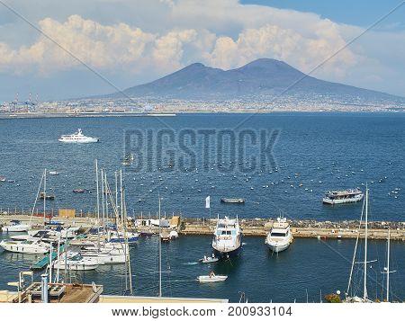 Naples Italy - August 7 2017. Yachts moored in Borgo Marinari harbor of Megaride island. mount Vesuvius volcano in background. Naples. Campania Italy.
