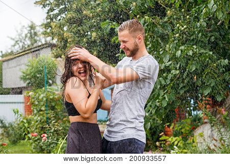 Young beautiful white couple bathing in the rain at the country house. The girl and her boyfriend laugh happily and frolic. Drops of water flow down their bodies.