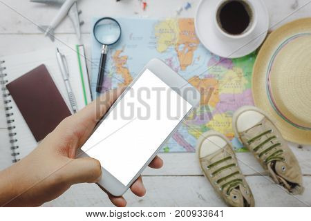 Top view / Flat lay hand using mobile phone on blur accessories to travel.