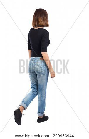back view of walking  woman. beautiful blonde girl in motion.  backside view of person.  Rear view people collection. Isolated over white background. A girl in a black sweater and jeans passes by