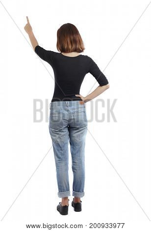Back view of  pointing woman. beautiful girl. Rear view people collection.  backside view of person.  Isolated over white background. A girl in jeans and a black T-shirt is pointing at the sky.