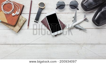 Top view accessories to travel concept.White mobile phone and headphone on wooden background.airplane map passport watch on wood table.