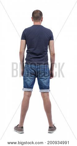 Back view of young manin shorts looking.  Rear view people collection.  backside view of person.  Isolated over white background. The guy in the denim shorts is standing with his back