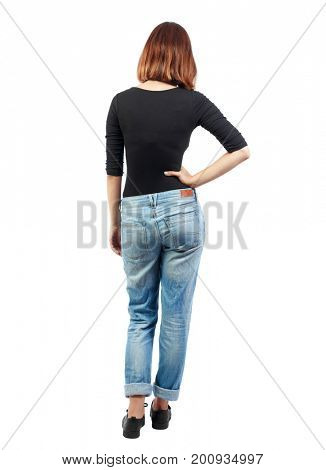 back view of standing young beautiful  woman.  girl  watching. Rear view people collection.  backside view of person. A girl in jeans and a black T-shirt is standing with her hand in her side.