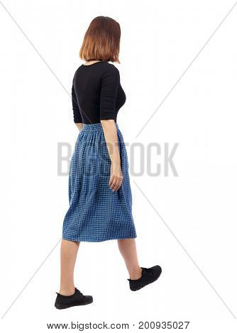 back view of walking woman in dress. beautiful girl in motion. backside view person.  Rear view people collection. Isolated over white background. The girl in the blue plaid skirt is going to right