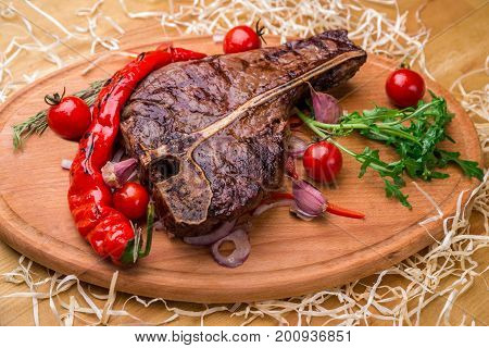 Appetizing Steak On A Bone, With Tomatoes, Pepper, On A Wooden Board. Horizontal Frame