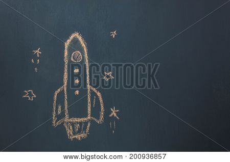 Top view / Flat lay Handmade drawing rocket ship launch / take off to the space with star on the blackboard by chalk board.