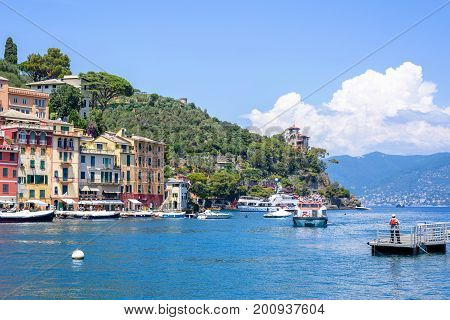 Beautiful daylight view to ships on water and buildings in Portofino city of Italy. Tourists walking on sidewalk.
