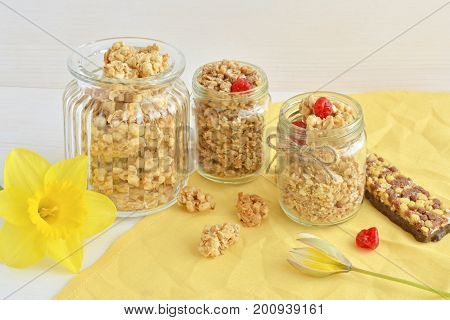 oat crunchy and crispy muesli bar with yellow spring flowers, over table background, healthy breakfast concept