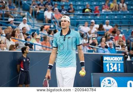 Mason Ohio - August 13 2017: John Isner in a first round match at the Western and Southern Open tennis tournament in Mason Ohio on August 13 2017.