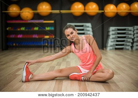 A full-length photo of a sexy and beautiful woman is doing physical exercises on a gym background. An attractive female is doing stretching or warming-up on the floor. Healthful lifestyle.