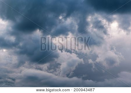 In the sky the storm clouds and the clouds. Bad weather. Strong wind and feeling the rain. The clouds are dark blue. The clouds are lit by sunlight.