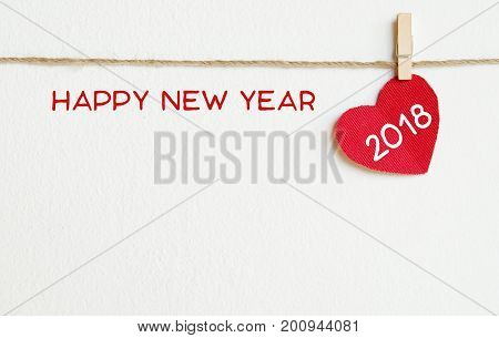 Red fabric heart with happy new year 2018 word hanging on the clothesline over white wall background new year template