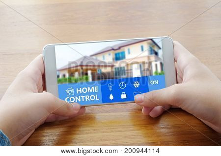 Hand using smart phone with home control device on screen background smart home concept internet of things
