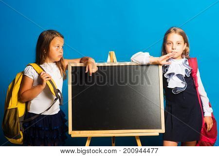 Children hold big schoolbags copy space. Schoolgirls with serious faces stand near blackboard. Girls in school uniform on blue background. Education and school concept.
