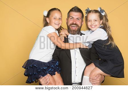 Schoolgirls With Smiling Faces Hug Man With Beard