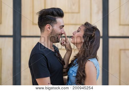 Happy woman touching her boyfriend's nose with love