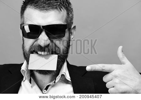 Man With Dark Beard Holds Green Business Card In Teeth