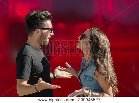 Young couple arguing and gesticulating on red wall