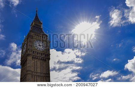 Big Ben, London, UK. A view of the popular London landmark, the clock tower known as Big Ben, showing 3pm as the time set against a blue and cloudy sky.
