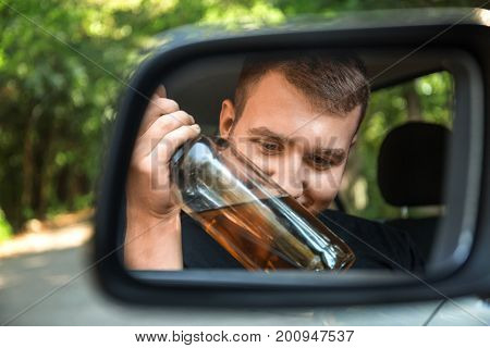 Close-up picture of a boozed young man with a bottle of beer in a rearview mirror on a blurred natural background. An addicted, irresponsible student driving with an alcoholic drink.