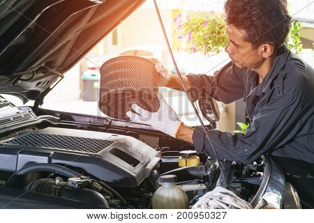 The technician removes the car's air filter for inspection and cleaning Automotive industry and garage concepts.