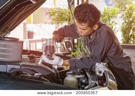 The technician is pouring the engine oil into the engine of the car Automotive industry and garage concepts.