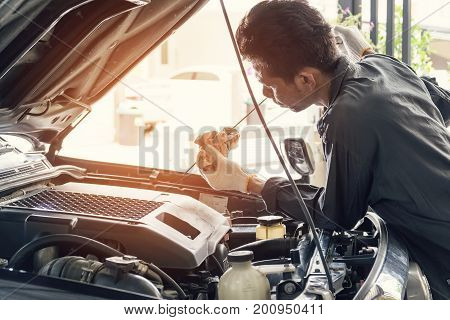 Car mechanic in grey uniform are checking the level of the engine oil Automotive industry and garage concepts.