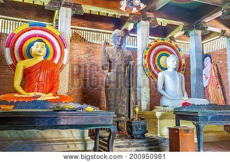 OKKAMPITIYA SRI LANKA - DECEMBER 2 2016: The interior of image house of Dematamal vihara decorated with statues of meditating and fearless buddhas on December 2 in Okkampitiya