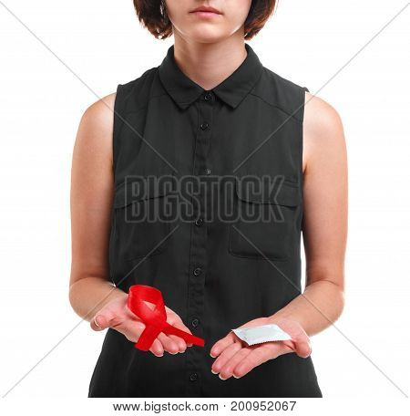 A red ribbon and a packed condom in hands of a brunette girl isolated on a white background. A young woman in a black shirt showing a symbol of solidarity, healthcare and a condom for safe sex.