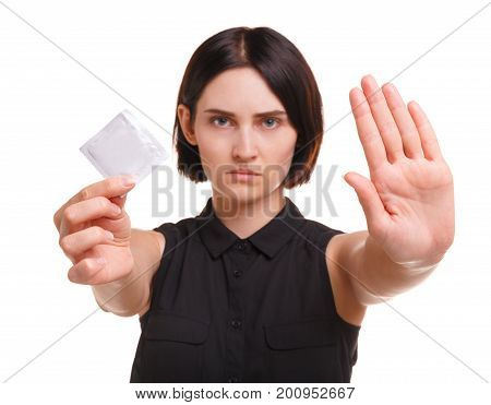 A young brunette woman holding a packed white condom. Portrait of an aware, modern brunette female in a black blouse with a contraceptive protesting against unsafe sex isolated on a white background.