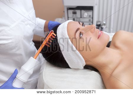 The Doctor-cosmetologist Makes The Procedure Microcurrent Therapy On The Hair Of A Beautiful, Young