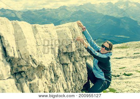 Attractive brunette rock climbing. Bouldering in nature.