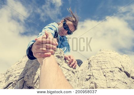 Female climber giving a helping hand. Teamwork and help concept.