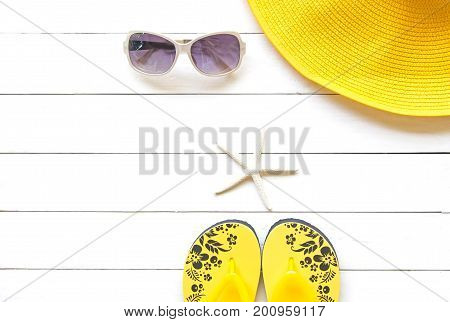 Summer Fashion woman yellow big hat and accessories in the beach. Tropical sea.Unusual top view colorfull background. Summer Concept.
