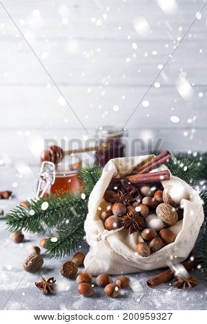 Fresh whole nuts and spices spilling out of a rustic hessian sack onto pristine fresh winter snow amidst decorative pine needles with copyspace for your seasonal greeting