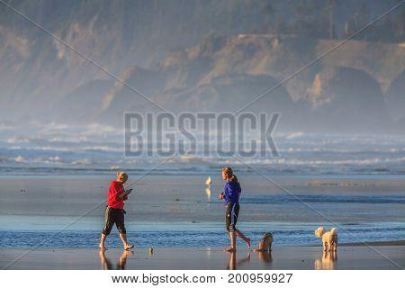 CANNON BEACH, OREGON, USA - SEPTEMBER 25, 2010: Woman walking dog on the Oregon Coast