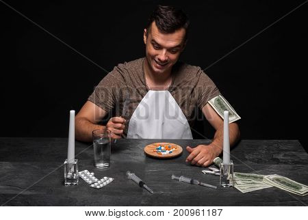Drug-dependent teenager sitting at the table. A guy with a drug addiction on a black background. A young man in a T-shirt and a white bib eating drugs from a plate. Drug addiction concept. Copy space.