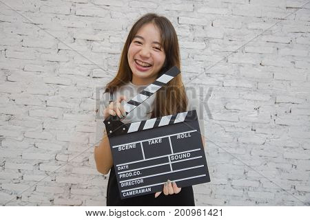 Portrait of a beautiful young Asian woman with clapperboard, she holding clapperboard, Film production and movie making concept