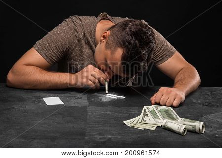 A hopeless man with a drug addiction and a lot of money on a saturated black background. A drug-dependent male sitting at the table. A guy uses narcotics. Fear, depression, abuse, addiction concept.