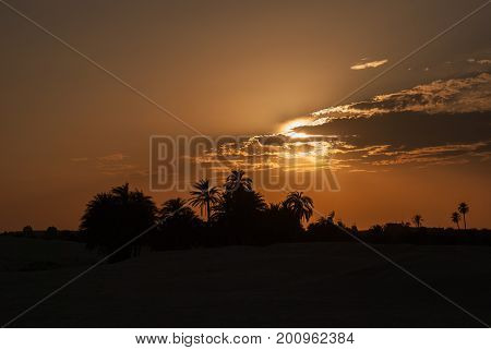 Orange sunset with beautiful clouds in the desert with a dark silhouette of an oasis