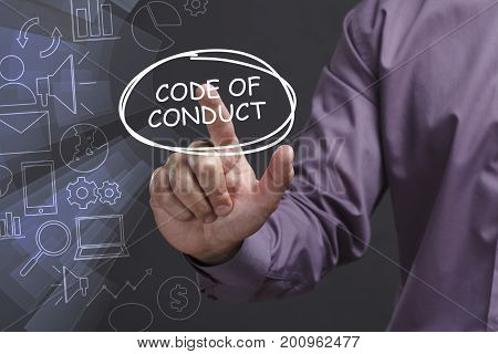 Business, Technology, Internet And Network Concept. Young Businessman Shows The Word: Code Of Conduc