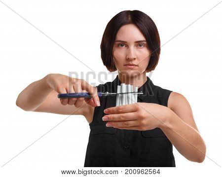 An attractive and health aware young woman is cutting cigarettes with scissors. Girl protesting against addictive nicotine isolated on a white background. Dangerous, harmful addictions concept.
